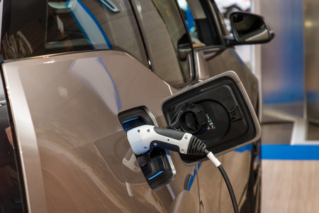 i3: BERLIN - NOVEMBER 07, 2013: Showroom. Electric plug (electric charge) of BMW i3 (Mega City Vehicle) The BMW i3 is a five-door urban electric car developed by the German manufacturer BMW. Editorial