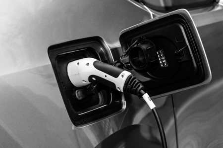 i3: BERLIN - NOVEMBER 07, 2013: Showroom. Electric plug (electric charge) of BMW i3 (Mega City Vehicle) The BMW i3 is a five-door urban electric car developed by the German manufacturer BMW. Black and white.