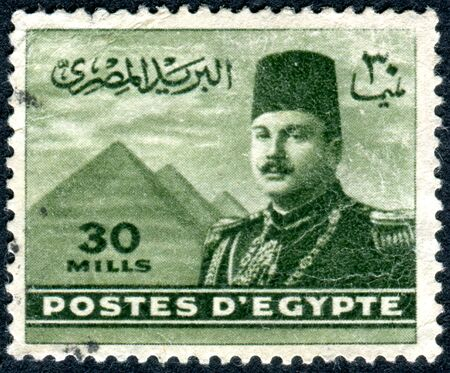 farouk: EGYPT - CIRCA 1947: A stamp printed in Egypt, shows the King Farouk in front of the Pyramids of Gizeh, circa 1947
