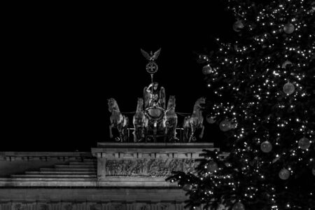 quadriga: A fragment of the Brandenburg Gate (Quadriga close-up) and a fragment of a Christmas tree in the foreground. Black and white.