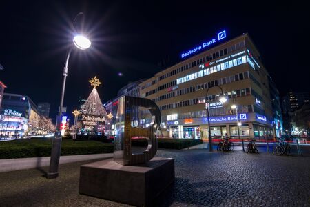 BERLIN - DECEMBER 07, 2016: The shopping street of West Berlin, Tauentzienstrasse in the Christmas illuminations. In the foreground is sculpture To B Remembered by International Auschwitz Committee.