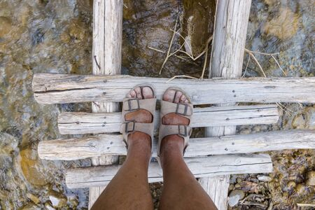pieds sales: A fragment of a wooden deck across the river. Dirty feet in sandals. View from above. Banque d'images