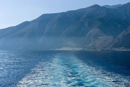 going in: Mountains of southern coast of Crete. Waves (traces of movement) of the ship going in the distance.