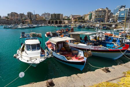 HERAKLION, GREECE - JULY 16, 2016: Crete. Moored fishing boats in the seaport. In the background the citys neighborhoods. Editorial