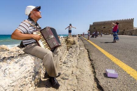 HERAKLION, GREECE - JULY 16, 2016: Crete. Musician on the waterfront plays accordion. In the background Venetian fortress.