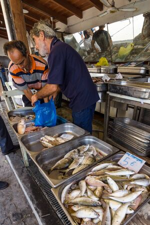 seller: HERAKLION, GREECE - JULY 16, 2016: Crete. The buyer and the seller. Fish market in Heraklion, near the seaport. Editorial