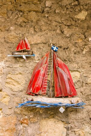 ship with gift: HERAKLION, GREECE - JULY 16, 2016: Sale of traditional local souvenirs in the historic center of the city. Wooden sailboat.