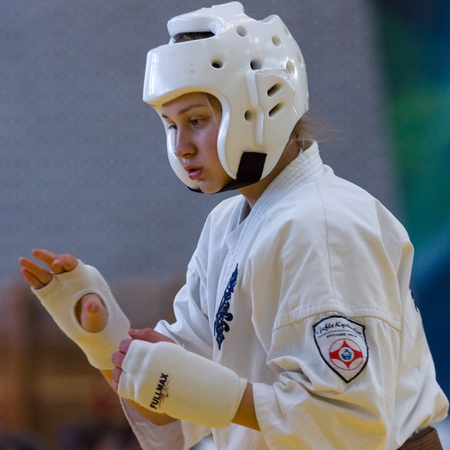 world championships: BERLIN - MARCH 18, 2017: Girl-fighter in a protective helmet, close-up. European championship Kyokushin World Union (KWU) for Children and Youth.