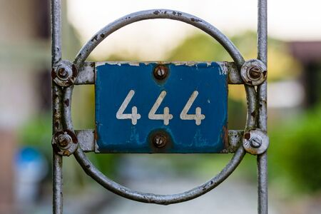 Plate with numbers 444 on the old fence. Stock Photo