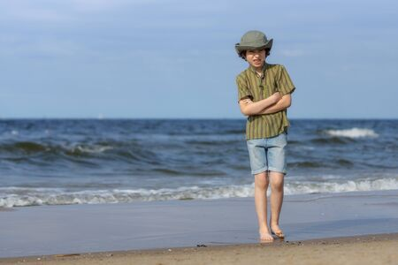 The boy stands on the sandy shore of the sea and freezes from the cold.