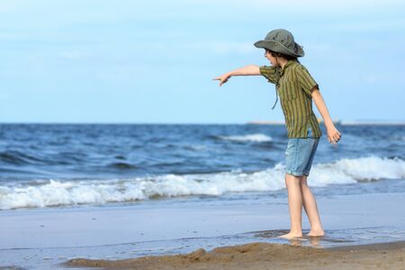 A boy stands on the sandy beach of the sea and points out into the distance with his hand. Stok Fotoğraf