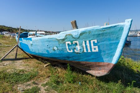 SOZOPOL, BULGARIA - AUGUST 24, 2017: An old fishing boat on the shore at the seaport. Editorial