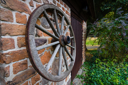 A wooden wheel from a cart hangs on a brick wall. Stock Photo