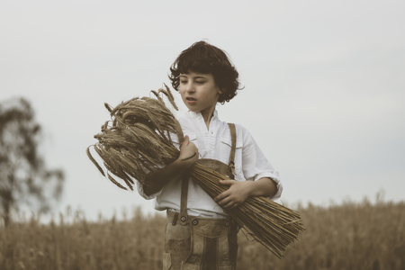 A boy in traditional Bavarian clothes stands in the field and holds a sheaf of rye in his hands. Harvesting. Vintage toning.