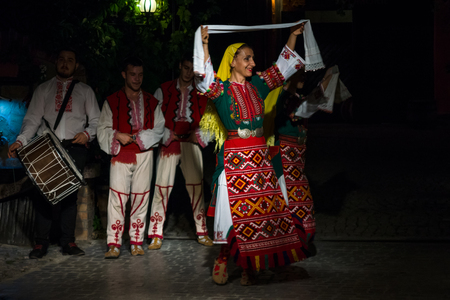 POMORIE, BULGARIA - AUGUST 27, 2017: Performance of artists for the visitors of the restaurant. Traditional Bulgarian dance in national costumes in Izbata's oldest restaurant.