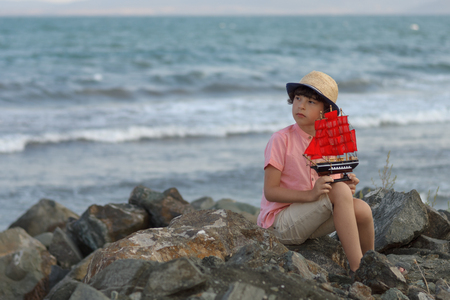 The boy sits on a stony seashore, holds a toy sailboat in his hands and looks into the distance.
