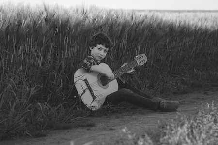 A boy in jeans and a shirt is sitting in the field with a guitar. Black and white. Matte stylization. Foto de archivo