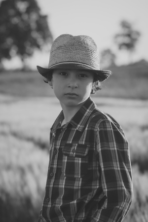 Portrait of a boy in a hat and shirt close-up. Black and white. Matte stylization.