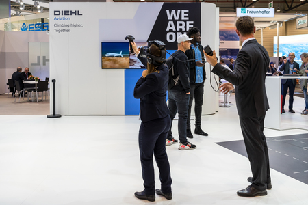 BERLIN - APRIL 26, 2018: Stand of Diehl Aviation. The visitor will test the virtual reality system. Exhibition ILA Berlin Air Show 2018