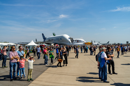 BERLIN - APRIL 28, 2018: Visitors to the exhibition on the airfield. In the background, outsize cargo freight aircraft Airbus A300-600ST (Super Transporter) or Beluga. Exhibition ILA Berlin Air Show 2018. Editorial