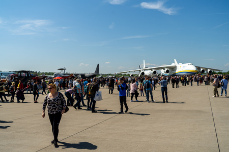 BERLIN - APRIL 28, 2018: Visitors to the exhibition on the airfield. In the background, strategic airlift cargo aircraft Antonov An-225 Mriya. Exhibition ILA Berlin Air Show 2018.