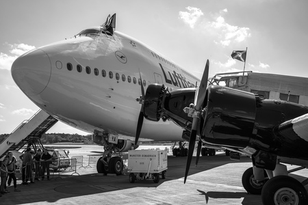 BERLIN - APRIL 28, 2018: Transport aircraft Junkers Ju 52/3m (foreground) and the widebody jet airliner Boeing 747-8 (background). Lufthansa. Black and white. Exhibition ILA Berlin Air Show 2018.