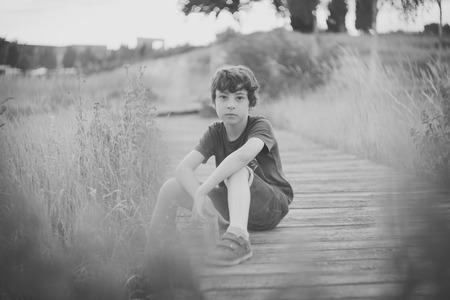 Portrait of a boy sitting on a wooden dais. Black and white. Reklamní fotografie