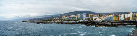 PUERTO DE LA CRUZ, SPAIN - JULY 19, 2018: Panoramic view of the rocky coast of a popular tourist town on the island of Tenerife, Canary Islands. Stock Photo - 110050428