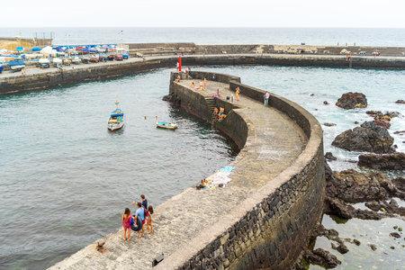 PUERTO DE LA CRUZ, SPAIN - JULY 19, 2018: Embankment and a small seaport. Rocky coast.
