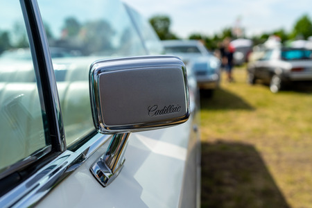PAAREN IM GLIEN, GERMANY - MAY 19, 2018: Rearview mirror of a full-size luxury car Cadillac de Ville convertible (third generation), 1968. Die Oldtimer Show 2018.