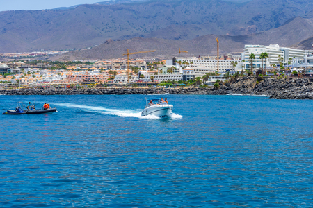 COSTA ADEJE, TENERIFE, CANARY ISLANDS, SPAIN - JULY 26, 2018: Hotels and houses on the popular coast of the resort. View from the ocean.