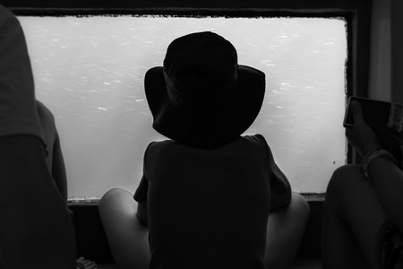 The boy is watching the underwater world through the large porthole below of  the waterline a tourist ship. Black and white. Фото со стока