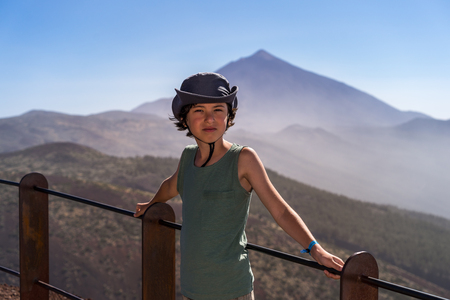 Portrait of a boy in a hat and t-shirt against the background of the volcano Teide. Tenerife. Canary Islands. Spain. Фото со стока