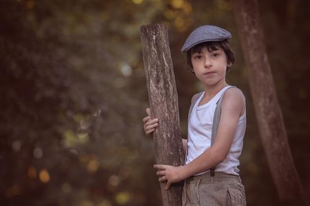 Porträt eines Jungen in Hosen mit Hosenträgern und einem ärmellosen Hemd vor dem Hintergrund der Natur.