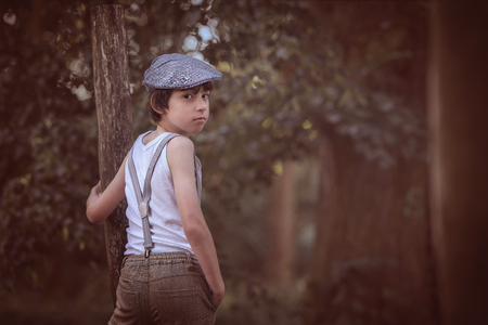 Portrait of a boy dressed in pants with suspenders and a sleeveless shirt, against a background of nature.
