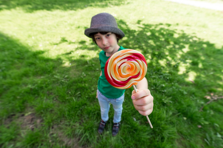 Joyful boy holding a lollipop in his hands. Wide-angle lens distortion. Focus on the foreground.