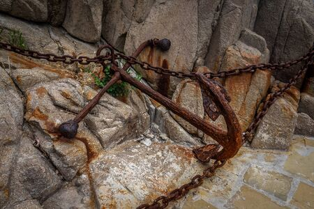 Old rusty anchor with chains on granite stones.