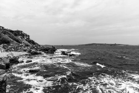The rocky coast of the Black Sea near the ancient city of Sozopol. Bulgaria. In the In the background are the islands of St. Peter and St. Ivan. Black and white.