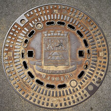 PLOVDIV, BULGARIA - JULY 02, 2019: Cast iron sewer cover with the emblem of the city. Plovdiv is the second largest city in Bulgaria.