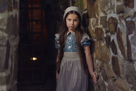 Frightened girl in the dungeons of an ancient castle.  Stylization. Vintage toning. 版權商用圖片