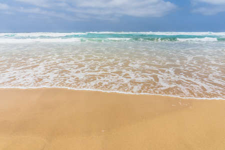 View of the ocean waves, sandy beach and sky.