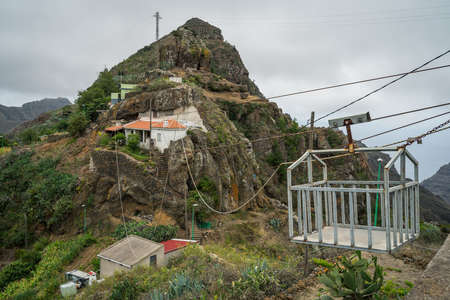 BEJIA, CANARY ISLANDS - JULY 06, 2021: House on the rocks. The mountain village of Bejia. Transport system for transshipment of goods. Editorial