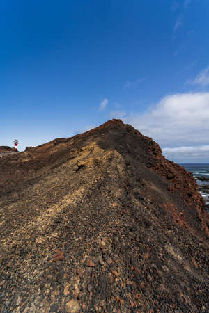 Rocky coast of the Atlantic Ocean at Cape Teno. A lighthouse in the background. Tenerife. Canary Islands. Spain.