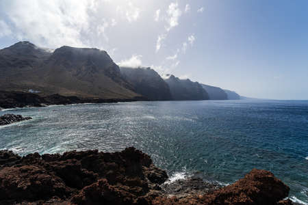 Rocky coast of the Atlantic Ocean at Cape Teno. In the background, the cliffs of Los Gigantes. Tenerife. Canary Islands. Spain.