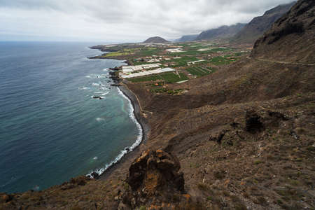 Rocky coast of the Atlantic Ocean. In the background, the small town of Buenavista del Norte. View from the observation deck - Mirador Punta del Fraile. Tenerife. Canary Islands. Spain.