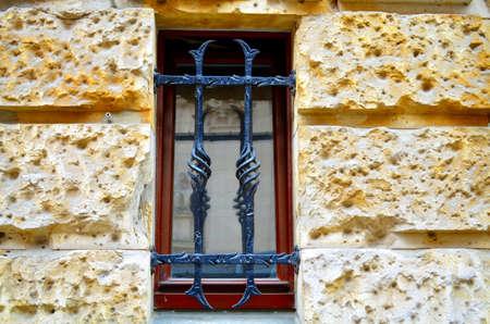 old metal: window with metal bars on street level