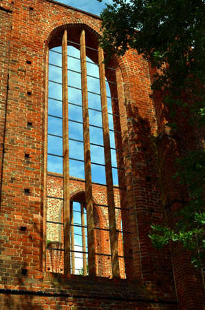 north window arch: ruin of an old monastery with blue sky in stralsund, germany Stock Photo