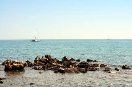 rocky coast at french riviera with sailing boat and blue sky