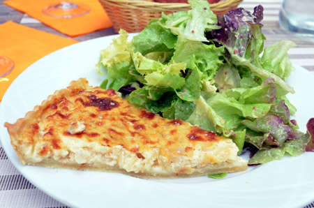 slice of typical french quiche with salad served on a plate