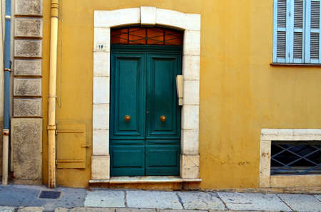 front house: green front door of a yellow house, french architecture
